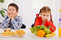 Kids with fast food and healthy food