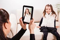 Mom taking photo of daughter with tablet