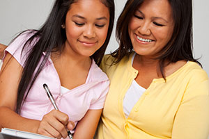 Girl and mom filling out paperwork at doctor's office