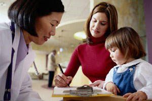 Mom and daughter filling out paperwork with doctor