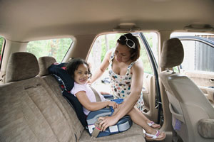 Mother securing daughter in booster seat