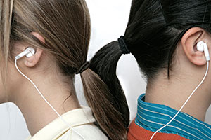 Teens sharing earbuds