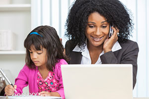 Mom on phone at laptop with daughter