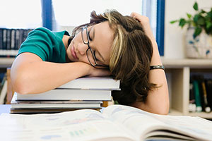 Teen girl sleeping on books