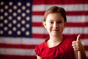 Girl giving thumbs up in front of an American flag