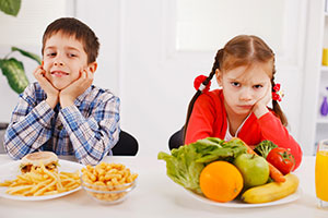 Boy and girl with fast food and vegetables