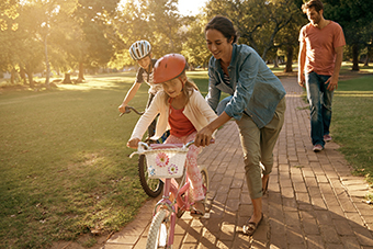 Parents teaching kids to ride bikes