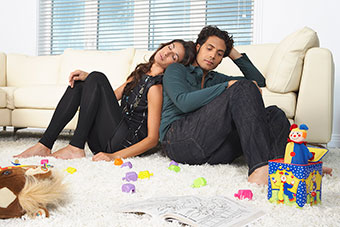 Tired parents sitting on the floor with kids' toys