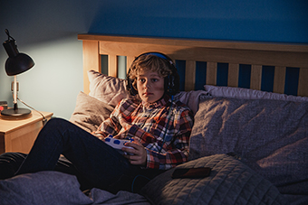 Boy playing video games in bed