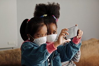 Young girls in masks taking a selfie