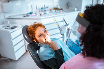boy in dentist chair pointing at tooth
