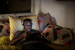 teen in bed with tablet