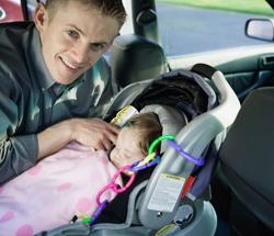 Dad securing baby in car seat