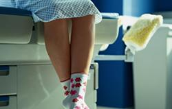 Girl sitting on examination table in hospital gown