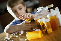 Young boy opening prescription bottles