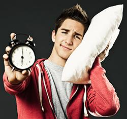 Teen with pillow and alarm clock